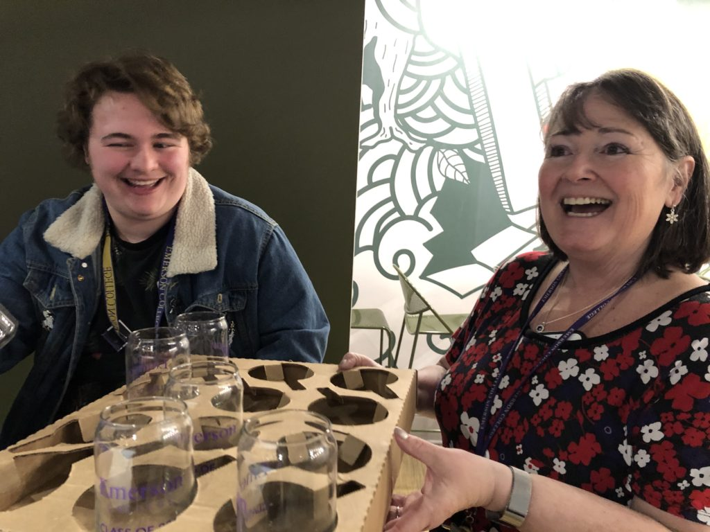 A man and woman laugh while she holds a box with drinking glasses