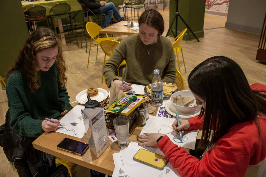 Three people sit at a table drawing with food on the table