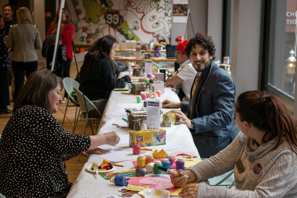 People paint and draw at a table