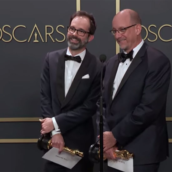 Andrew Buckland and Michael McCusker talk at a microphone after winning Oscars