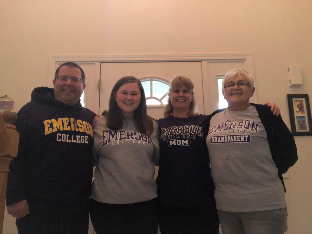Four people dressed in Emerson sweatshirts and shirts