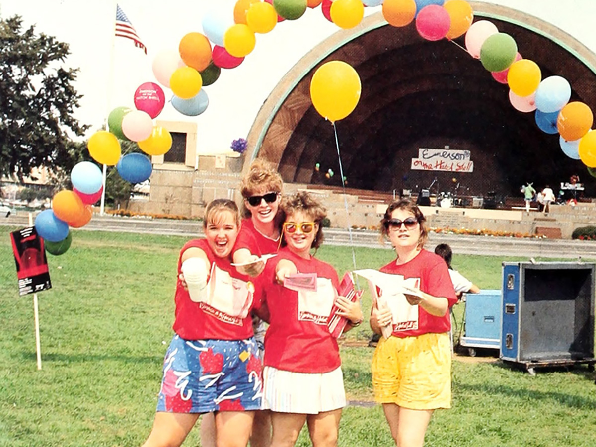 Four students stand in front of Hatch Shell