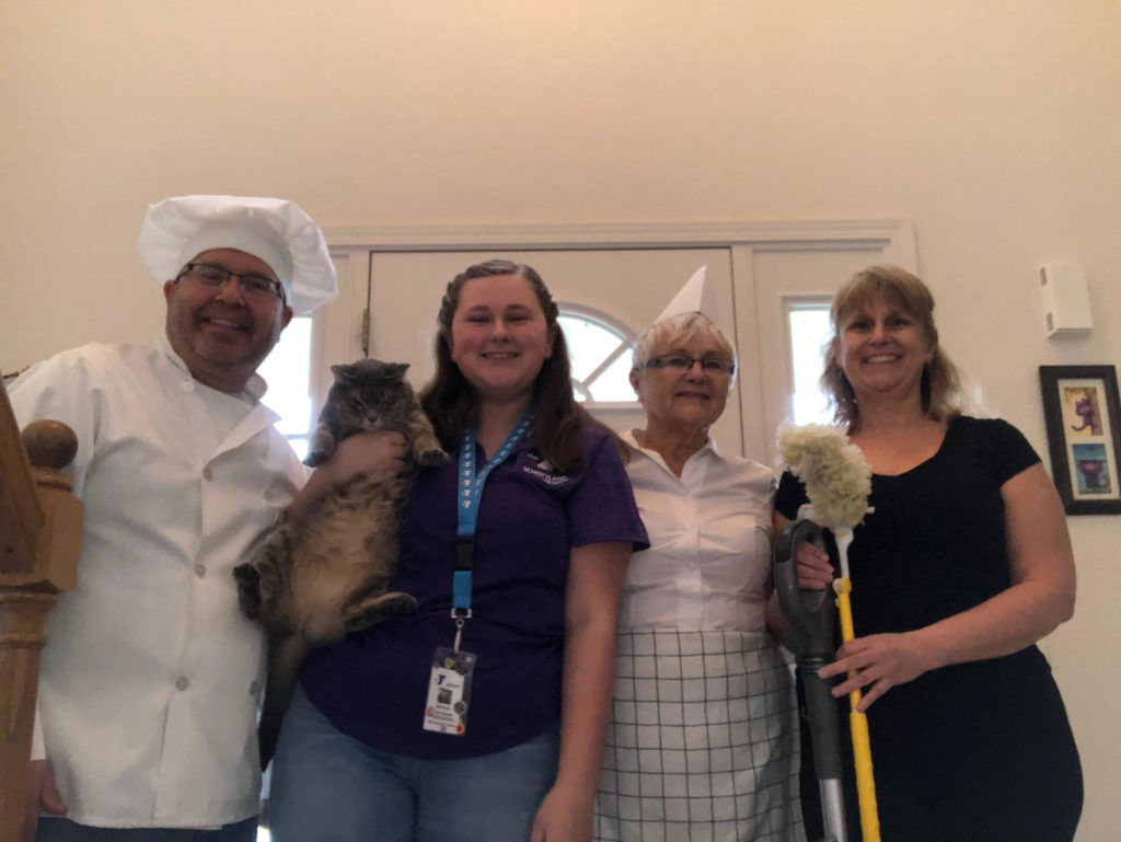 Four people dressed up wearing outfits from their first jobs. A chef, a veterinarian, a waitress, and a housecleaner.