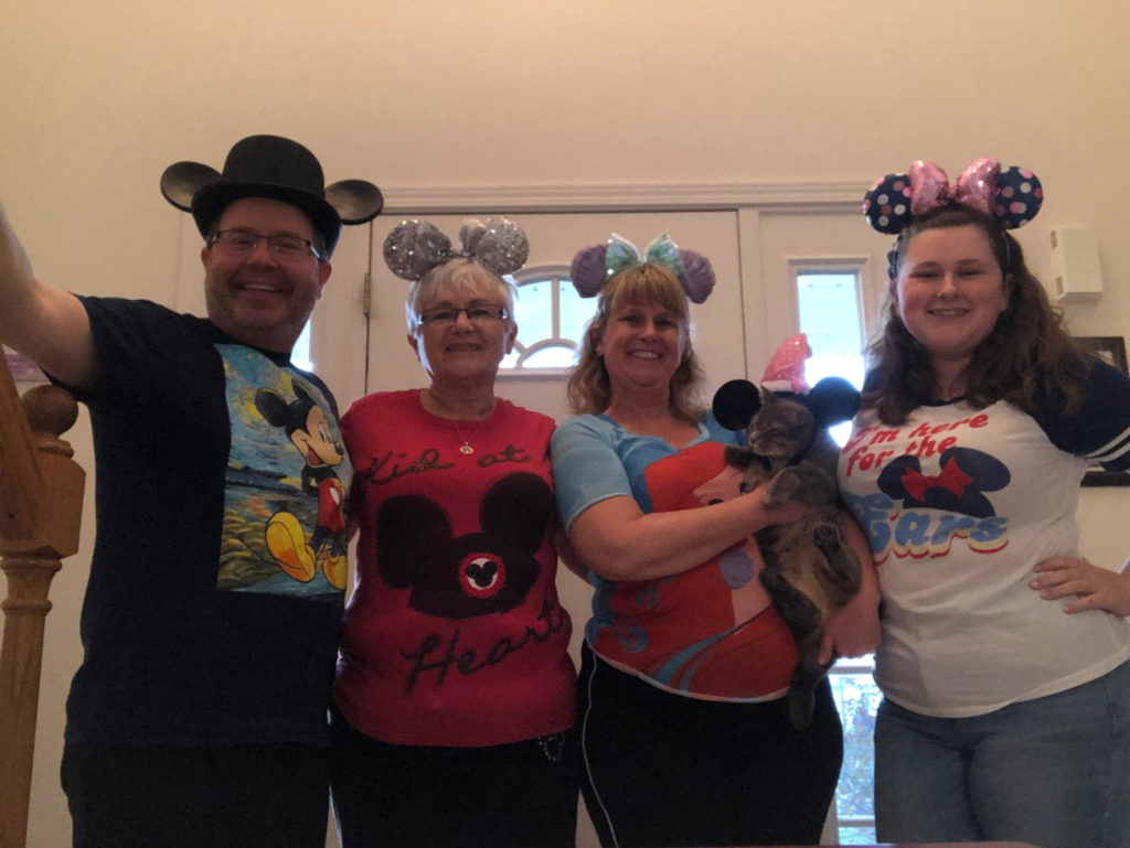 Four people dressed up wearing Disney shirts and mouse ears.