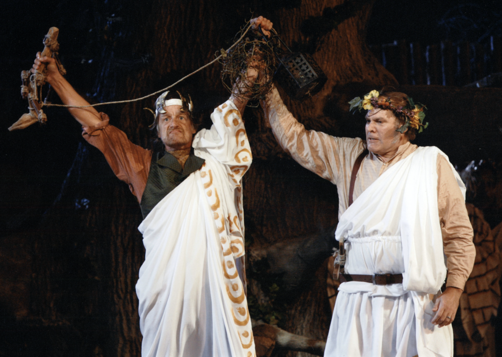 Two men in togas lift their hands together.
