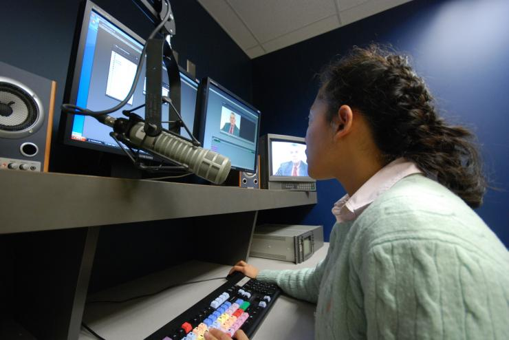 A person in a media studio looks at a screen with a microphone in front of them.