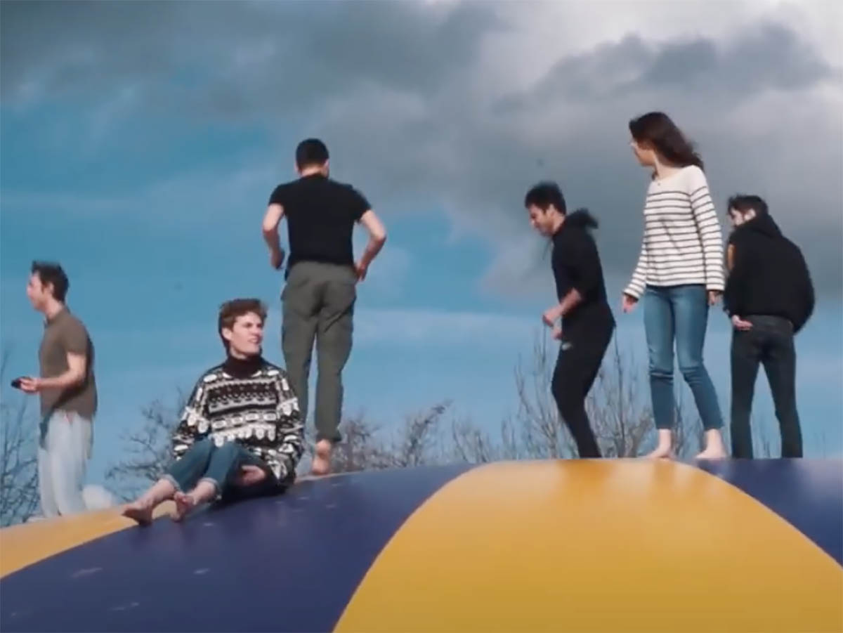 Six people atop a large bouncy ball