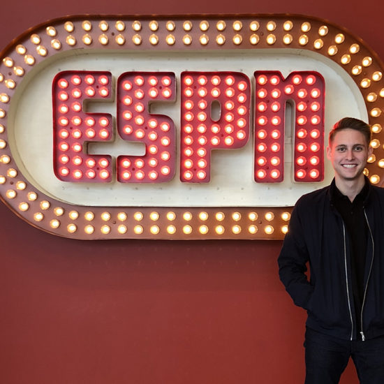 Zach Rothfeld stands in front of neon sign that says ESPN