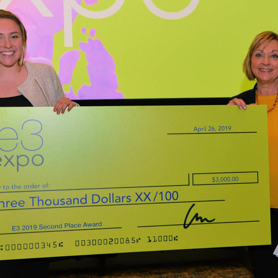 Two women stand with an oversized check