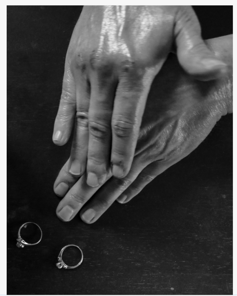 Closeup of a woman's hands with two wedding rings on a table.