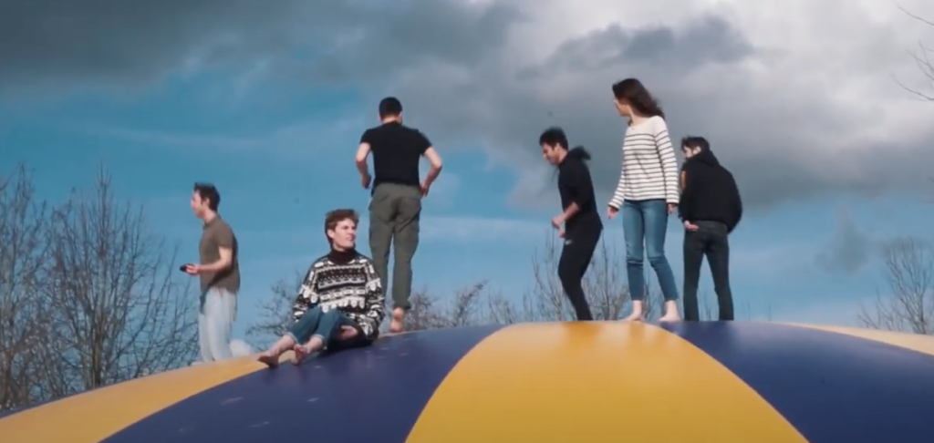 Six people atop a large inflated ballon.