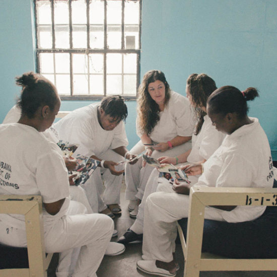 Five incarcerated women sit together.