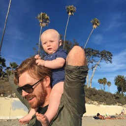 A man with a baby on his shoulders