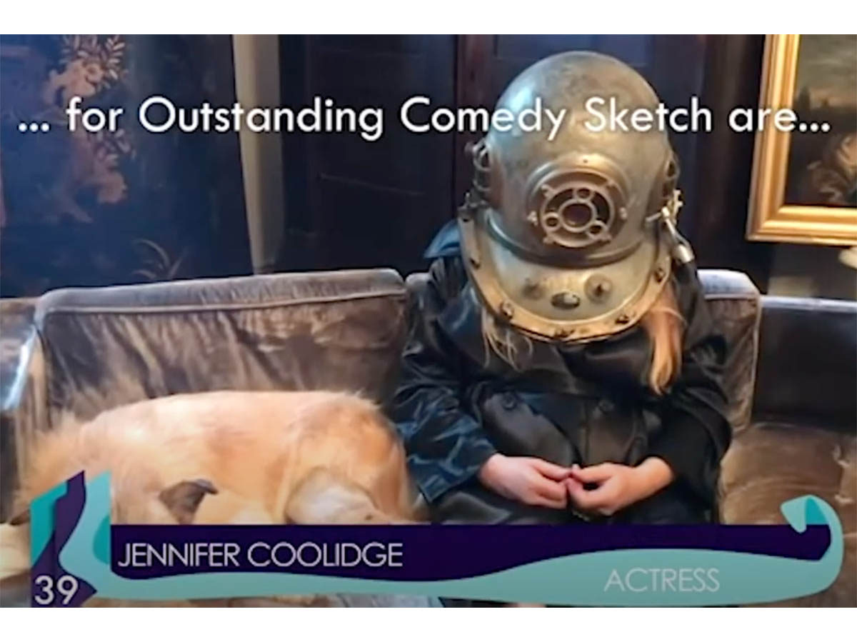 Jennifer Coolidge wears an old scuba scuba helmet while sitting on a couch with a dog