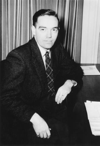 black and white photo of Charlie Klim at desk