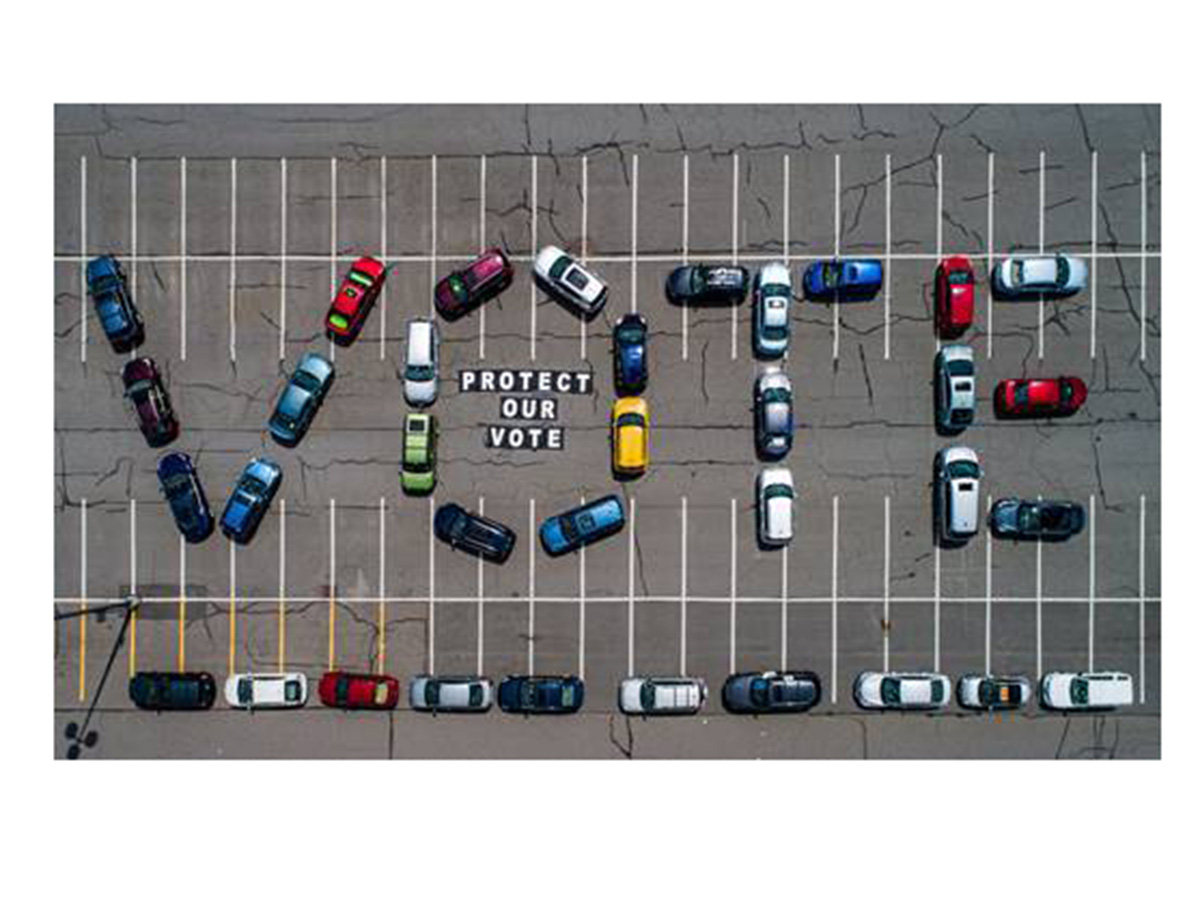 "cars in lot spell out ""vote"""