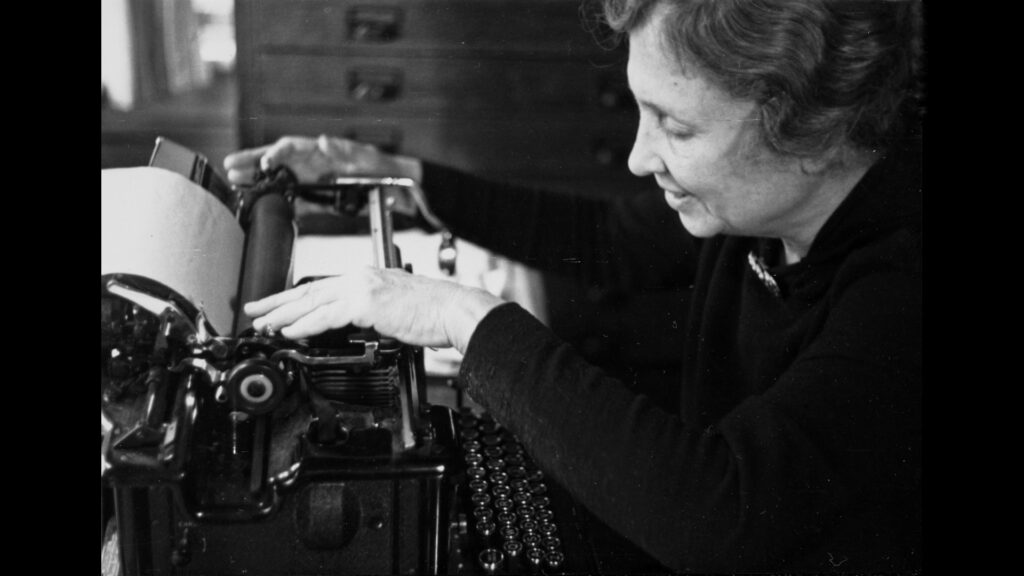 A woman touches a typewriter