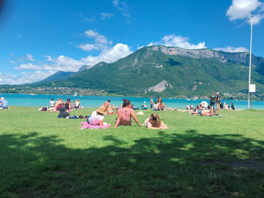 People sit on grass with water and green mountains in front of them.