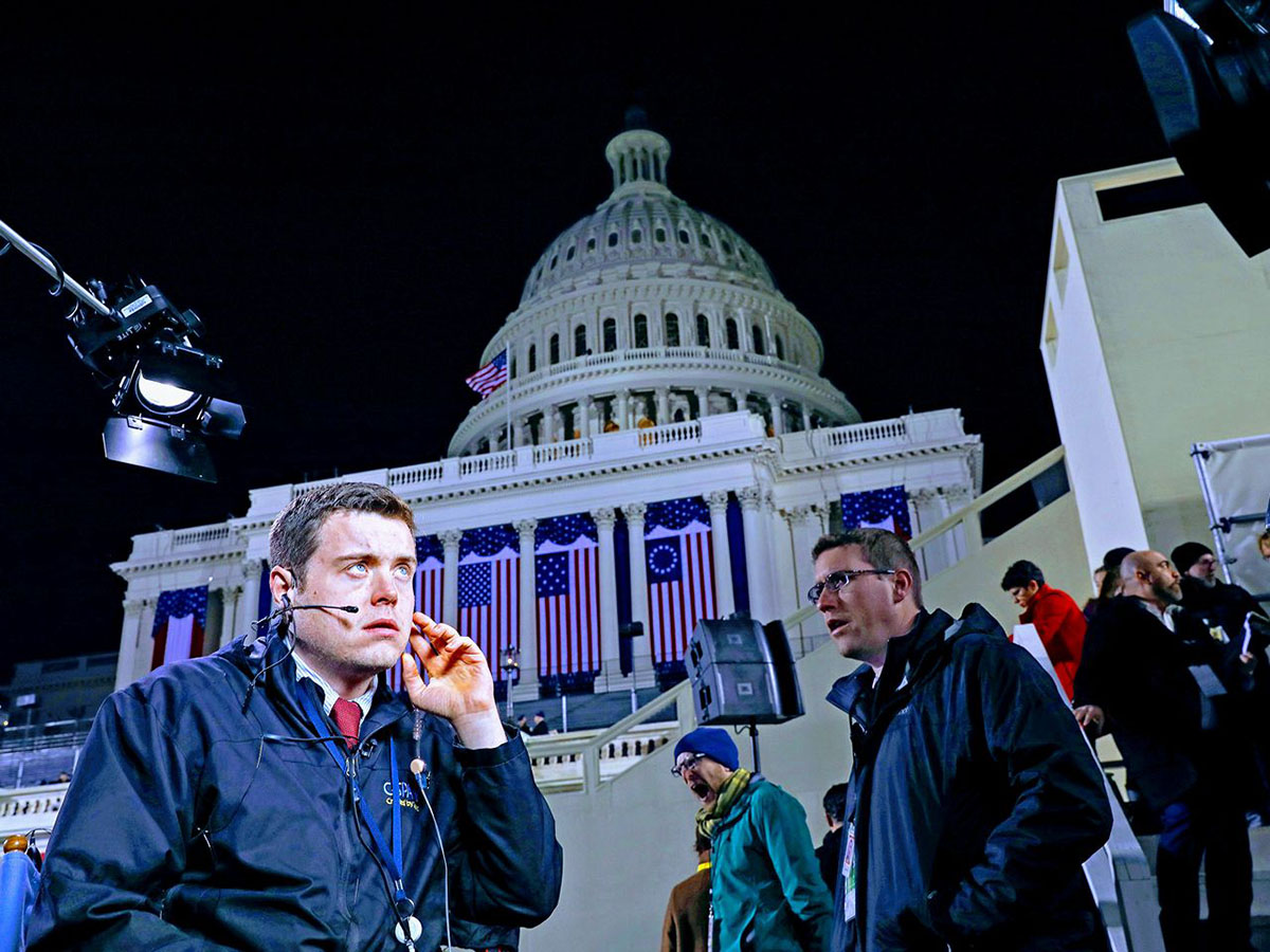 A man holding a headset on his head with the Capital building in Washington DC in the background.