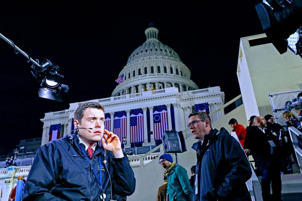 A man with a headset on his head with the Capital building in Washington DC in the background.