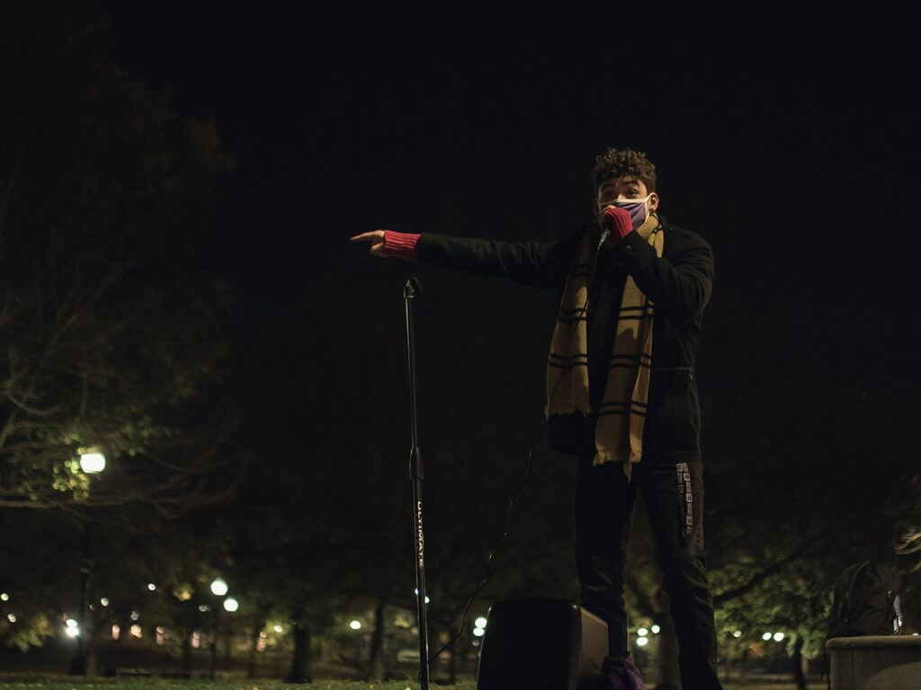 man in mask speaking into mic in Boston Common at night