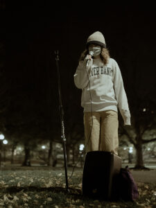 woman in mask talks into mic in Common at night