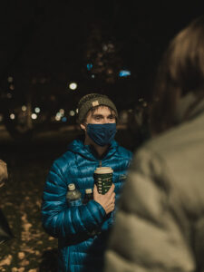 student in mask talks to student with back to camera