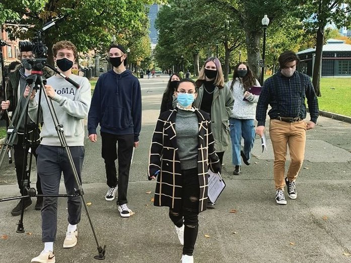 students in masks with film gear walking down street