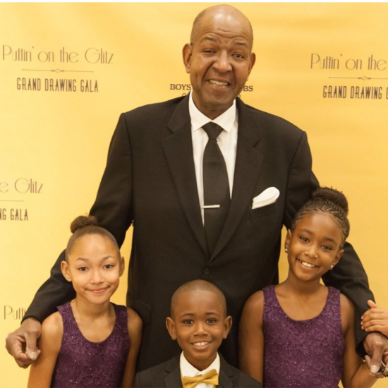A tall man stands in a suit with his arms around three children in front of him
