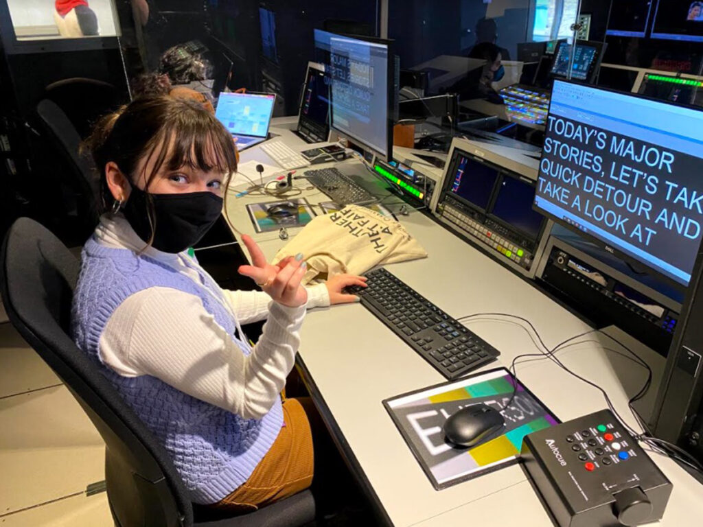 woman in mask behind control panel points at camera