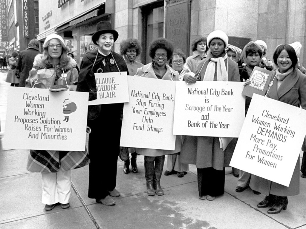 black and white photo of women holding signs in 1970s