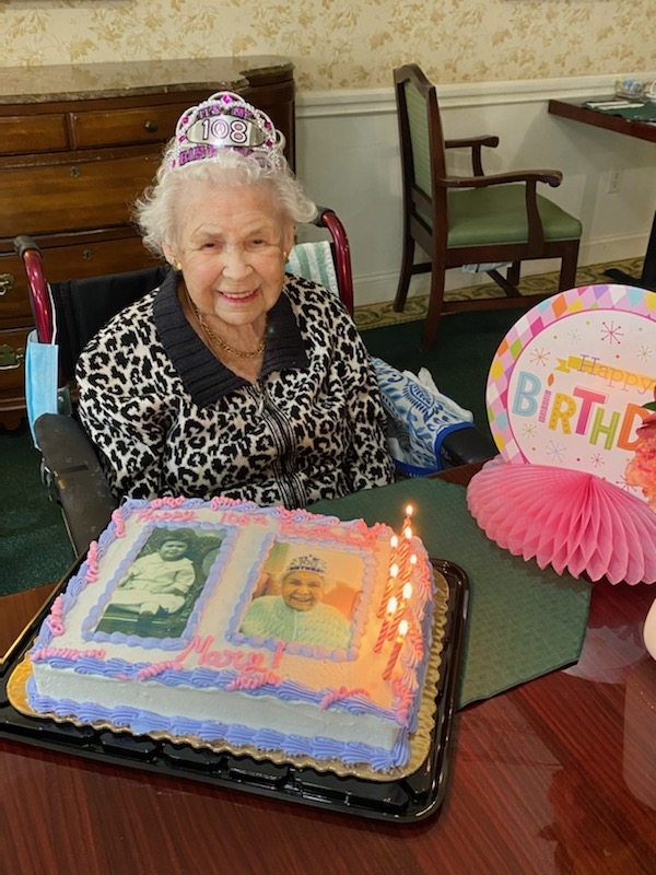 A woman sitting celebrating her 108th birthday with a cake in front of her.