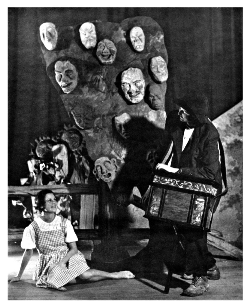 One woman on the ground, another stands, and another is wearing a created art piece with multiple heads on it as part of the play