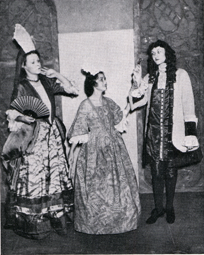Three people stand dressed in 1700s style dresses