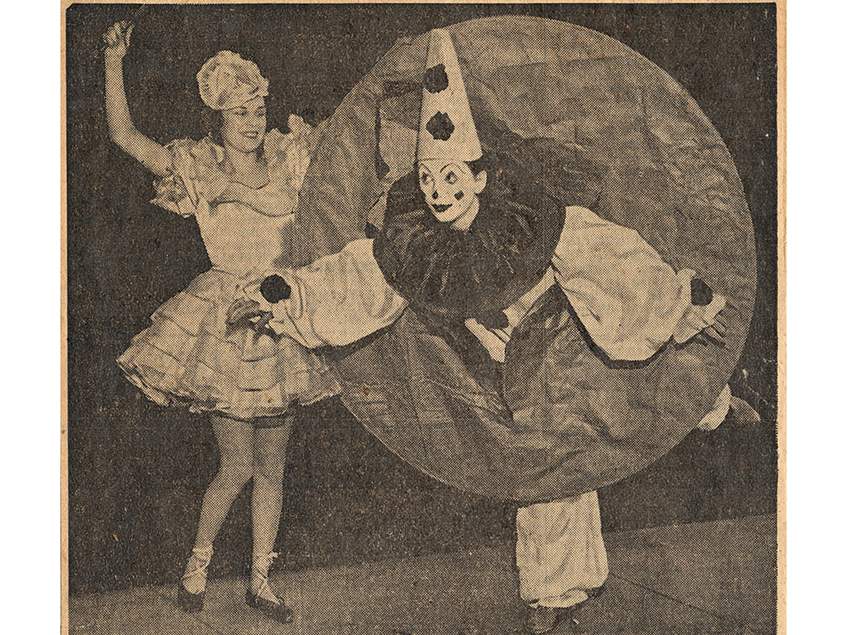 A woman stand while another woman is dressed as a clown standing on one foot