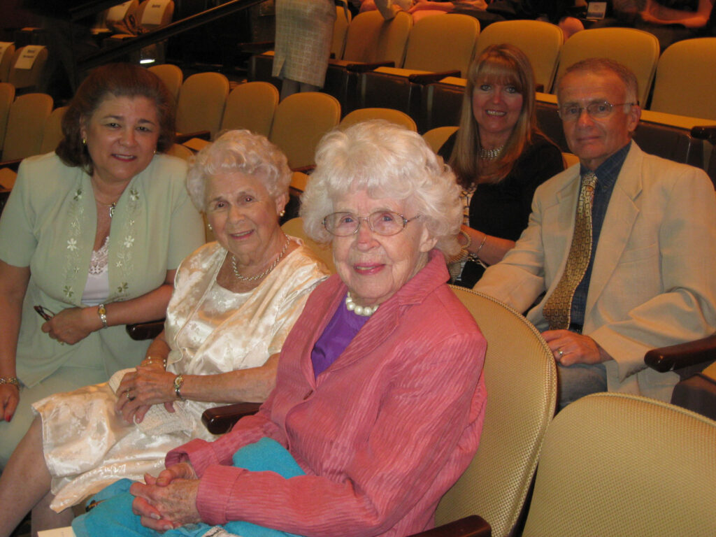 Five people sit together in an auditorium