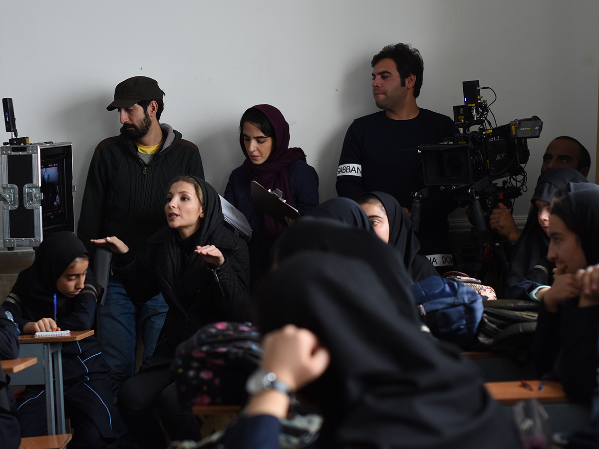 Hadad talking on set, surrounded by crew