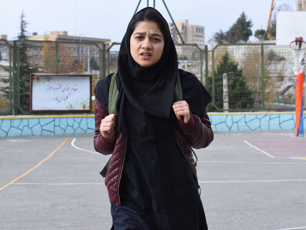 Girl in hijab with backpack in schoolyard