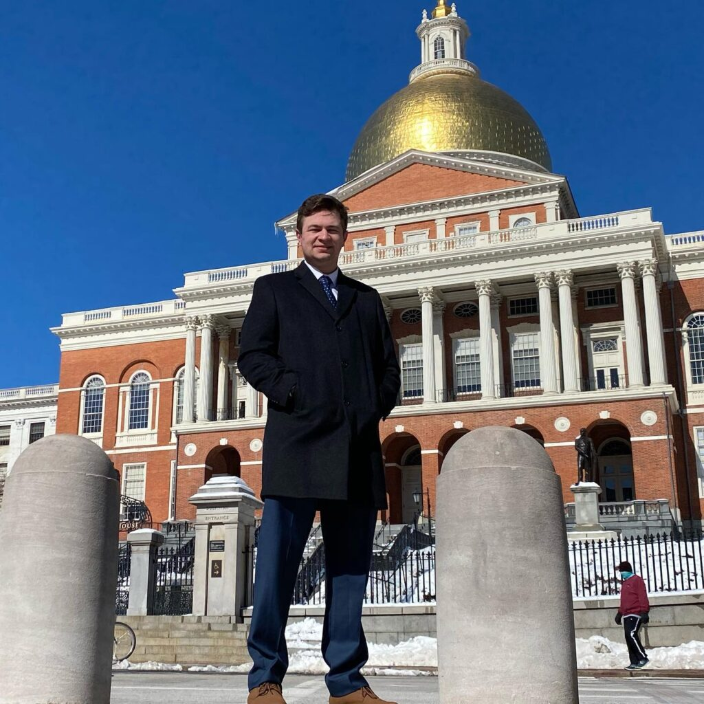 Man stands in front of Massachusetts State House