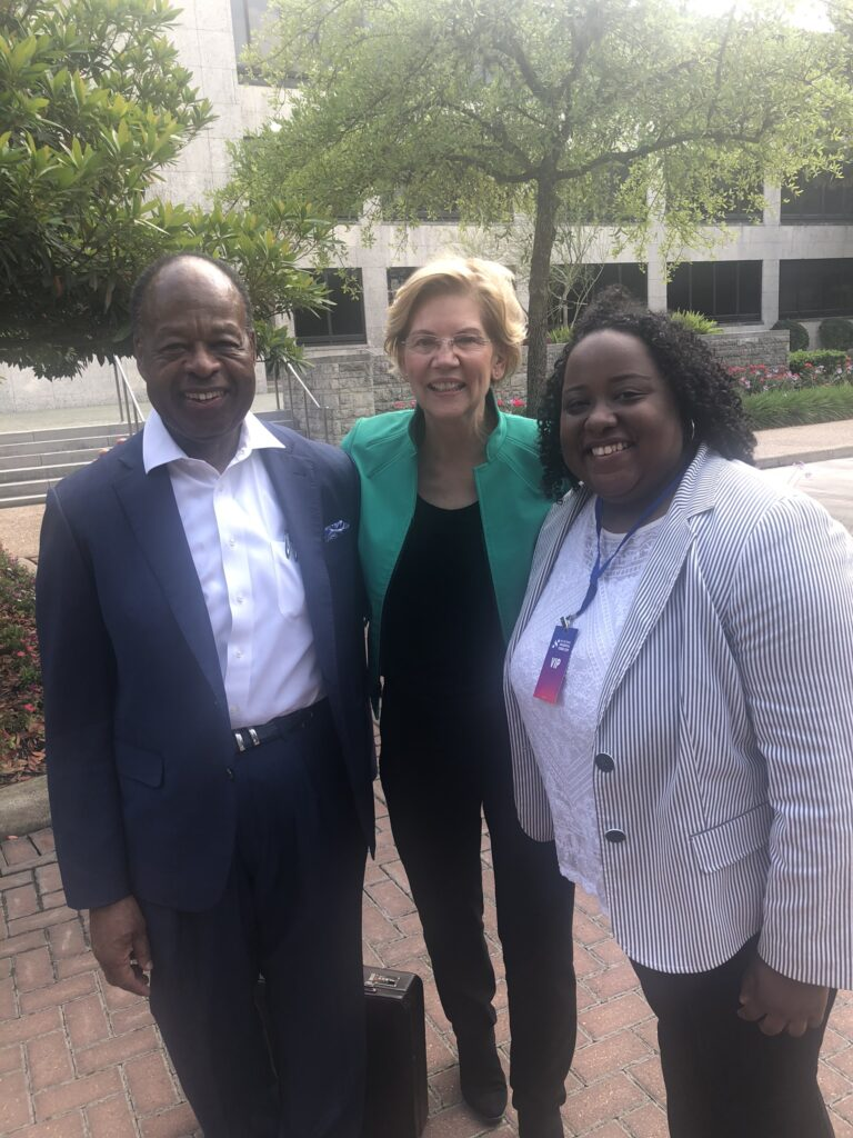 A man stands with two women