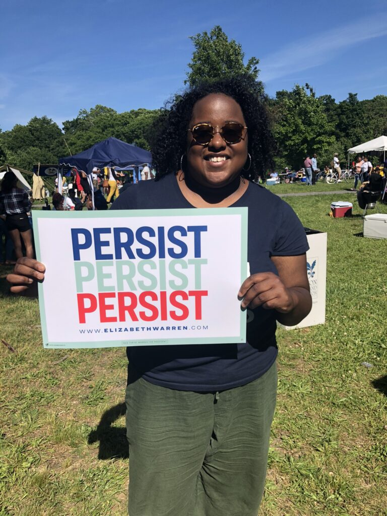 A woman stands holding a sign that says persist.