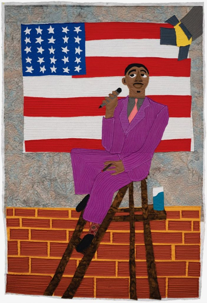 A quilt of a man sitting wearing a purple suit, sitting on a stool with an American flag behind him