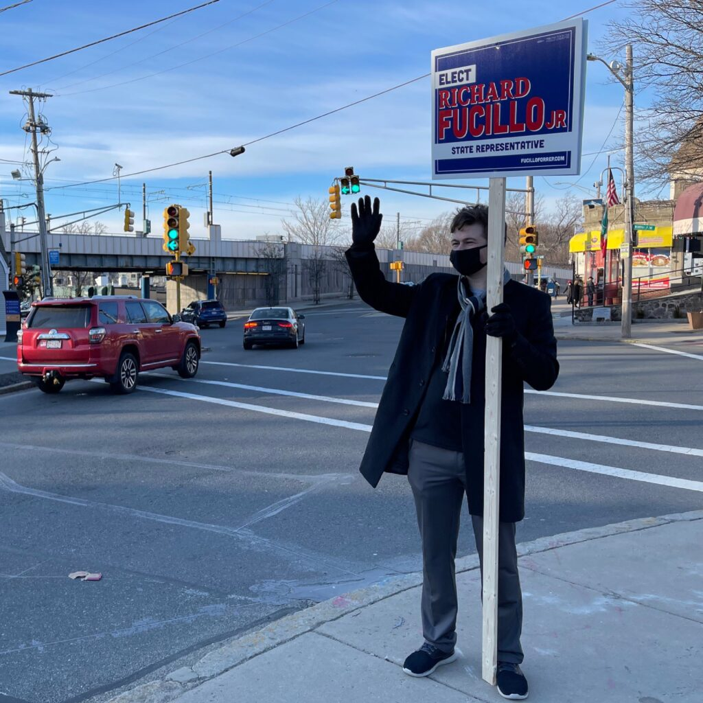 Man stands at corner of street holding campaign sign while vehicles drive by.