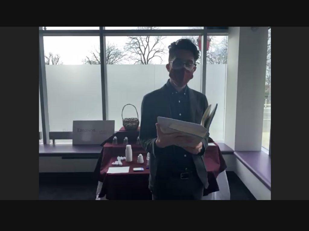 MJ Halberstadt reading in front of table, in front of window