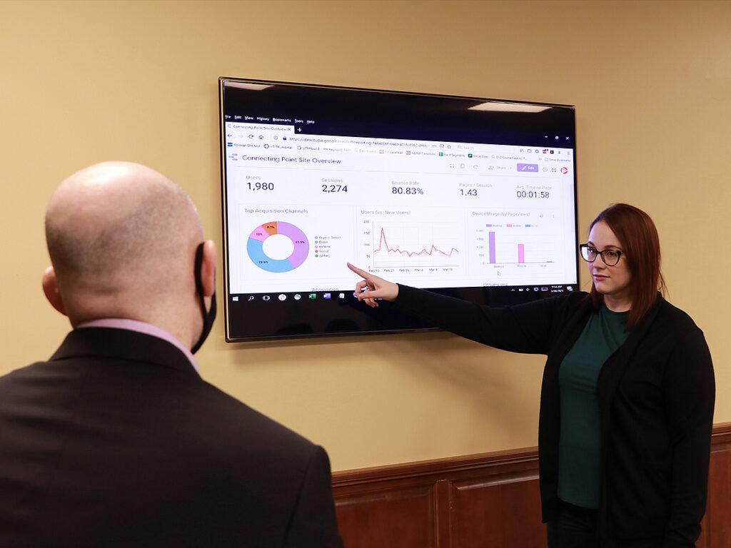 Rachel Scott points at data on screen