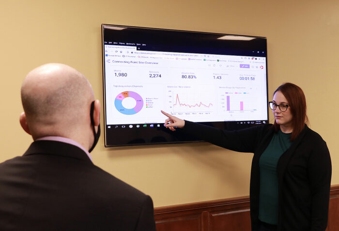 Rachel Scott points to data on screen