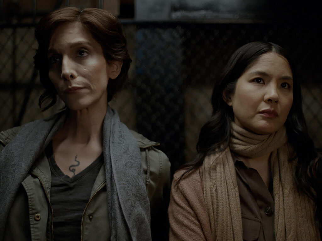 Two women standing in elevator looking in distance