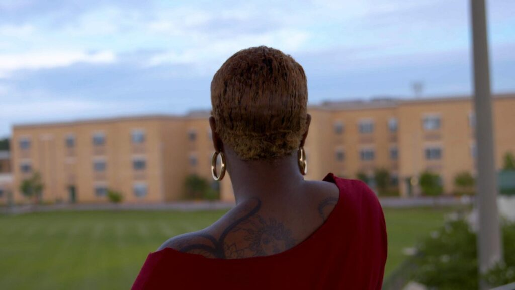 Black woman looking at school, back to camera