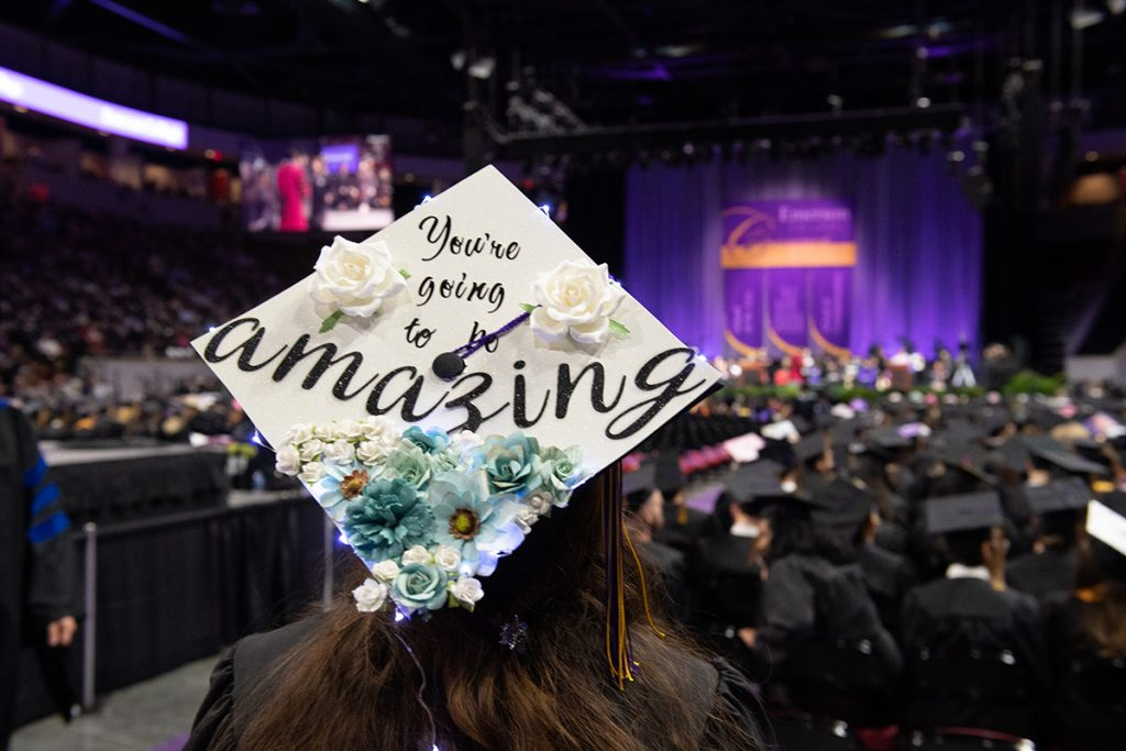 """woman with back to camera, mortarboard says """"You're gong to be amazing"""""""