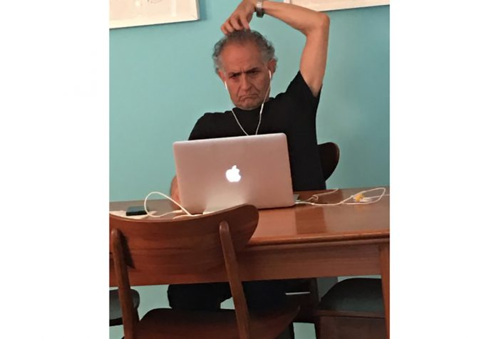 Man sits at table in front of laptop with hand on his head